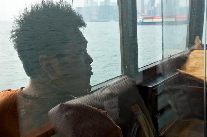 Silhouette d'un marin dans le poste de pilotage d'un navire circulant dans le Victoria Harbour. Hong Kong/Chine