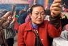 Femme venue brûler des bâtons d'encens et prier parmi la foule au temple de Wong Tai Sin à Kowloon. Hong Kong/Chine