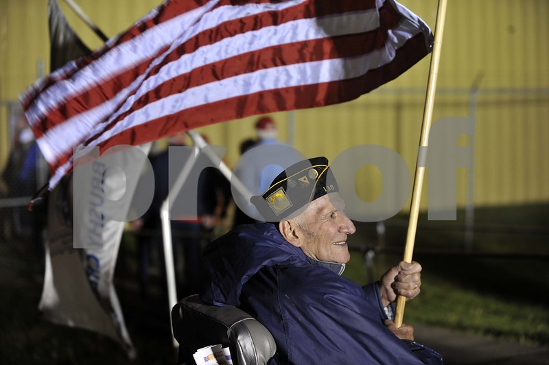 -Messenger photo by Hans Madsen<br /> <br /> Korean War veteran John Olmstead, of Fort Dodge, holds his U.S. flag Saturday morning as he greets veterans arriving at the Fort Dodge Regional Airport for the Brushy Creek Area Honor Flight.