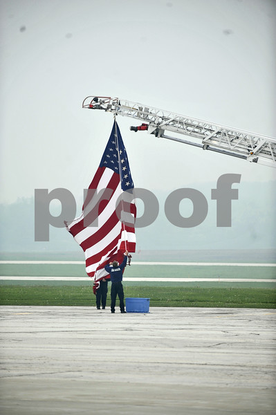 -Messenger photo by Hans Madsen<br /> <br /> Members of the Fort Dodge Fire Department take down the flag down from their truck Saturday morning after the Brushy Creek Area Honor Flight departure.