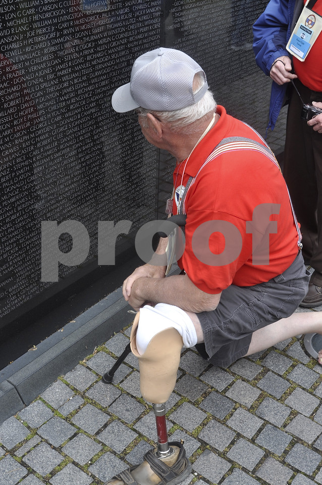 -Messenger photo by Chad Thompson<br /> <br /> Thomas Underberg, a Vietnam veteran from Carroll, kneels down as he views the names of fallen veterans at the Vietnam Veterans Memorial in Washington, D.C. Saturday. Several Vietnam veterans searched on the wall for fellow veterans they knew.