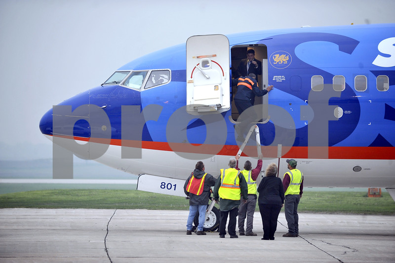 -Messenger photo by Hans Madsen<br /> <br /> A SunCountry aircraft mechanic gets help from the staff at the Fort Dodge Regional Airport to get back into the plane after he stayed on the ground to get the balky ladder stowed back into the aircraft.