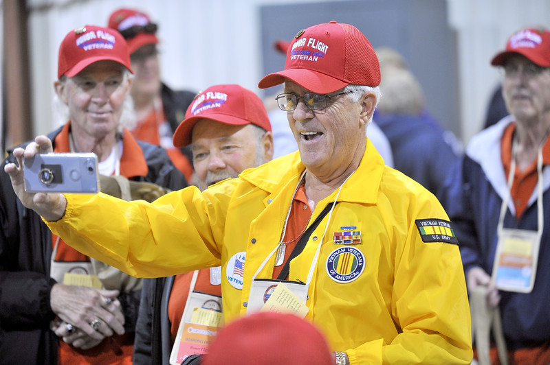 -Messenger photo by Hans Madsen<br /> <br /> Michael Monroe, of Spencer, takes a photo with his friend Terry Heinrichs, center and his brother, Dean Monroe, at left as they wait to board the Brushy Creek Area Honor Flight to Washington D.C. Saturday morning.