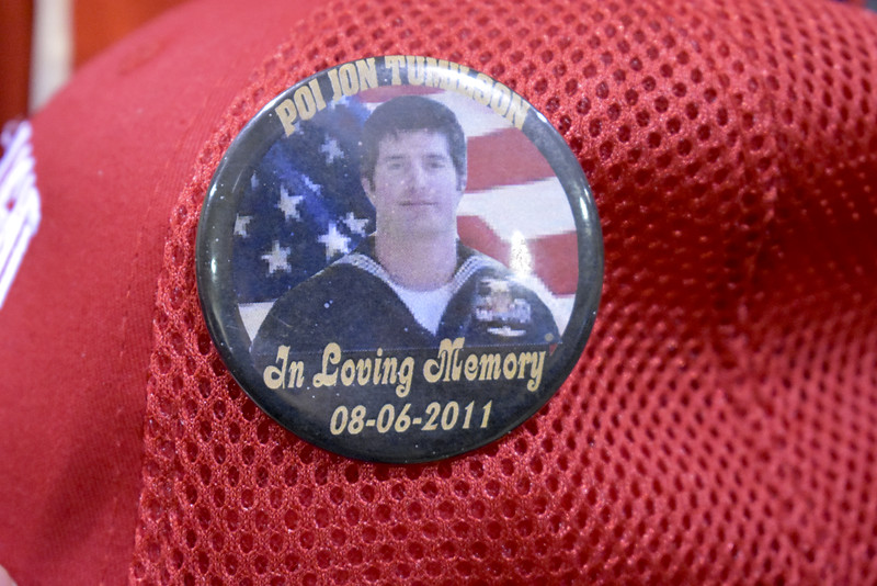 -Messenger photo by Chad Thompson<br /> <br /> A button honoring the life of Jon Tumilson, a U.S. Navy SEAL, is displayed on the hat of John Jacobs, a U.S. Army veteran of Manson. Tumilson is Jacobs' nephew. Tumilson died when the helicopter he was riding in was shot down in Wardok Province, Afghanistan, on Aug. 6, 2011. Thirty-one American lives were lost that day.