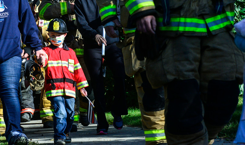 KRISTOPHER RADDER — BRATTLEBORO REFORMER<br /> Adler Bennett, 4, of Westminster, Vt., walks with the local firefighters the 3.43 miles in Bellows Falls, Vt., on Saturday, Sept. 12, 2020, to honor the 343 firefighters died during the 9/11 terrorist attacks.