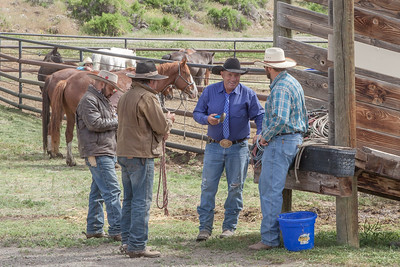 "Warren Johnson, second to the right,, owner of Hell's A""Roarin"" Outfitters, and members of his crew chat at the Gardiner Fairgrounds prior to the running of the horses up Crevice Mountain to the ranch.  This photo won Third Place in the People Category, Adult Advanced Division, Big Sky Country State Fair 2019, Bozeman, MT."