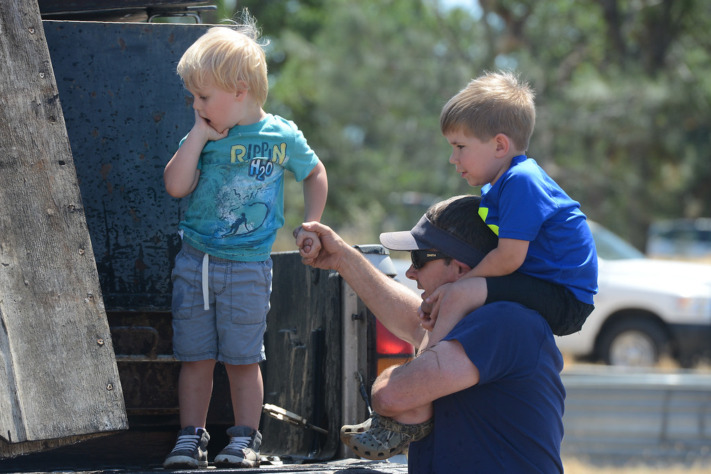 . Jett Bernedo, Chris Giampaoli and Lucas Caldwell watch as catfish are poured into Horseshoe Lake, May 18, 2018,  in Chico, California. (Carin Dorghalli -- Enterprise-Record)