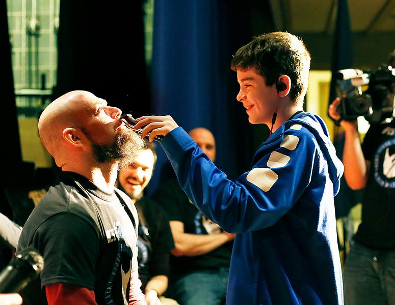 HOLLY PELCZYNSKI - BENNINGTON BANNER Hoosick Falls Central School teacher Adam Cabana tips his head back while getting shaved by 8th grader Jack Eastman.