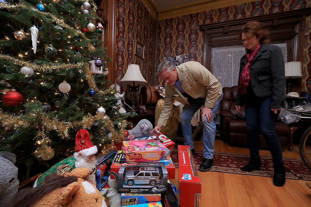 . Jack Hoover opened his home again this year for the annual Toys for Tots fundraiser he has put on for 11 years. David Lighthall and Lori Navaroli of Sterling place a toy under the tree. SENTINEL & ENTERPRISE/JOHN LOVE