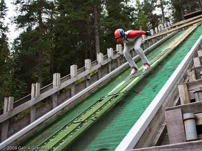 Down the inrun on watered plastic tracks in Gjerpenkollen K-74 in Drammen