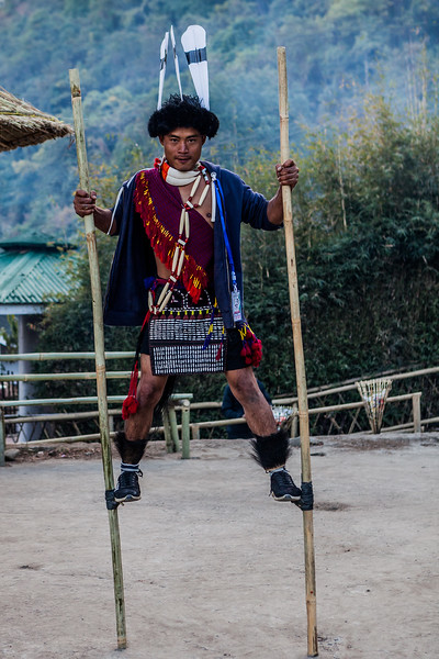An Ao man plays a game of stilt walking in his morung at the Hornbill Festival, Nagaland, India