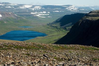 Horft niður í Rekavík bak Látur og Hálsavatn. Sjá má tilraun til vegagerðar, en upprunalega átti vegurinn að liggja út Rekavík og upp Öldudal.