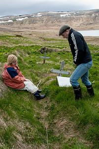 Guðmunda og Oddur fóru yfir kirkjugarðinn og leituðu að legsteinum í sinunni.