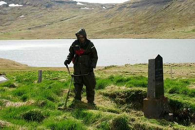 Sturla að slá í kirkjugarðinum.