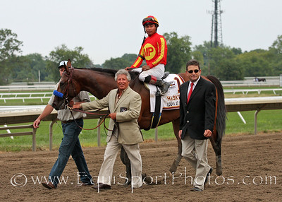 Champion racecar driver Mario Andretti leads Haskell winner Lookin at Lucky and Martin Garcia into the winner's circle at Monmouth Park 8/1/10 JH.