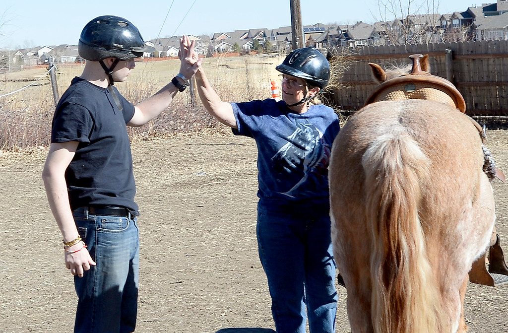 . David Wagner gets a high five from Pam Thode.  David Wagner works with trainer, Pam Thode, to get to know Chiquita the horse. Sunny Horse Foundation, a Broomfield nonprofit, wants to host a six-week horse therapy program in April that will benefit local veterans. Cliff Grassmick  Staff Photographer  February 16, 2017