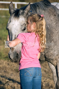 Little girl hugging senior appaloosa gelding