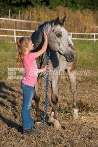Little girl petting senior appaloosa gelding