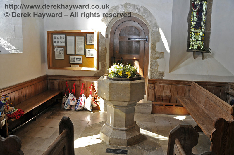 The display case to the left of the font commemorates Archbishop of Glasgow, Robert Leighton (1611-1684), a great scholar and builder of Christian unity, whose grave is prominent in the church curtilage just past the vestry door.   <br /> <br /> St Giles Church, Horsted Keynes 06.04.2013  6619