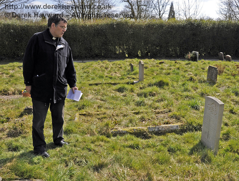 The Rector looking at the war grave of the young couple (Gunner and Mrs Knapp) killed together whilst walking on the railway track near Waterworks on 31st July 1943.  Just married, they were sheltering under a cape in a heavy storm and failed to hear a train approaching from behind them whilst they were taking a short cut back to the nearby Nobles Farm shortly after their wedding reception.  Signs of an accident were seen when the locomotive arrived at Horsted Keynes Station, and a search of the track revealed their bodies.   <br /> <br /> St Giles Church, Horsted Keynes.  06.04.2013  6599