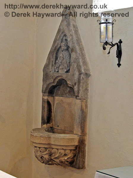 The small statue of the priest holding Bread and Wine over the piscine, used for washing the chalice, was placed above the original piscine recovered from the Tower wall as part of the 19th Century restoration of St Giles.  <br /> <br /> St Giles Church, Horsted Keynes 06.04.2013  6641