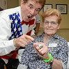 Boston Bruins national anthem singer Rene Rancourt strikes a pose with Resident Council President Betty Sandquist during the ribbon cutting ceremony for the Gardner Rehabilitation and Nursing Center on Wednesday afternoon.  SENTINEL & ENTERPRISE / Ashley Green