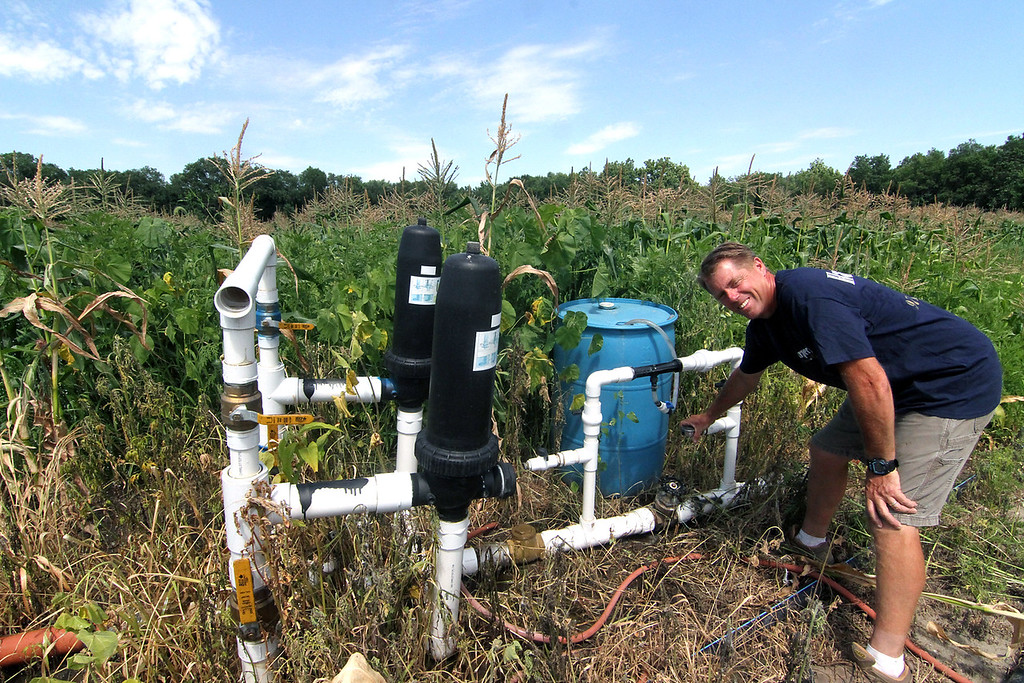 . Dave Harper owner of Harper Farms in Lancester, shuts off one of the valves in the irragation system at his farm. SEN/David H. Brow