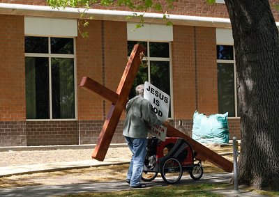 A man with a mission walks down 5th Street with a large cross and sign about Jesus Tuesday April 5, 2016 in Chico, Calif. (Emily Bertolino -- Enterprise-Record)