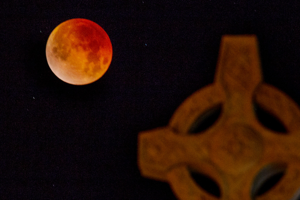 . The super blue blood moon in total eclipse hangs over the Celtic Cross of Saint Patrick\'s Church during the early morning hours in Larkspur, Calif. Wednesday, Jan. 31, 2018. (James Cacciatore/Special to the Marin Independent Journal)