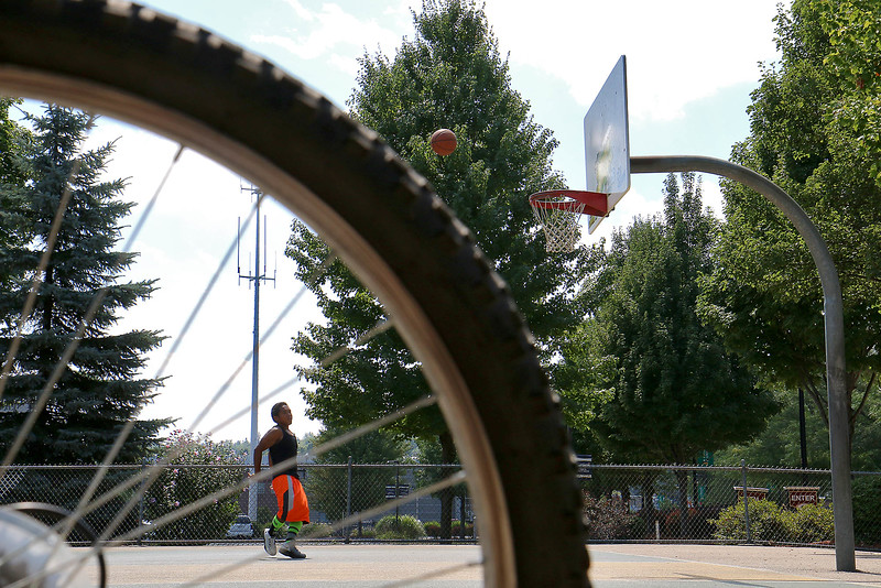 Toan Tran who grew up in Fitchburg and now lives in Minnesota did not let the heat bother him after he road his bike to the Green Street Park in Fitchburg on Thursday to shoot some baskets as the temperatures reached the low 90's. Tran was home visiting family and friends. SENTINEL & ENTERPRISE/JOHN LOVE