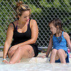 Kamila Caraballo, 4, of Leominster and her Mom Mickey Galilea of Leominster relax at the edge of the water at the J. Robert Crowley Swimming Comples at Coolidge Park in Fitchburg on Thursday as they try and stay cool in the 90+ heat. SENTINEL & ENTERPRISE/JOHN LOVE