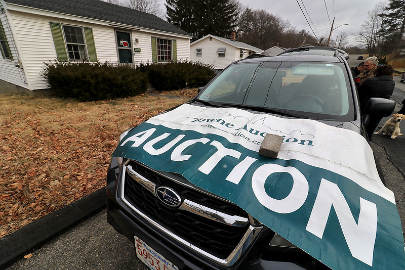 Jean Mitchell the owner of a house at 90 Sylvan Avenue in Leominster was fighting to have an auction on her home stop on Wednesday, January 10, 2019. A banner for the auction company Towne Auction is on the hood of a car in front of the house. SENTINEL & ENTERPRISE/JOHN LOVE