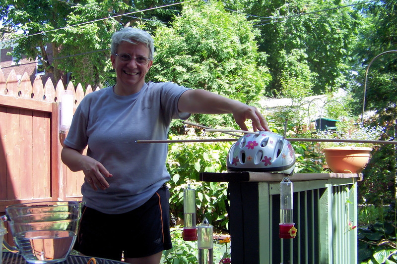 Jeane, chief photographer, assists by keeping the helmet stable while Patti prepares the big strawberry-shaped feeders that go on either side of the helmet.