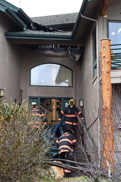 Loveland Fire Rescue Authority firefighters remove insullation and other debris as they mop up a house fire Monday, March 26, 2018, at 2101 Skyrock Rd. in Loveland. (Photo by Jenny Sparks/Loveland Reporter-Herald)