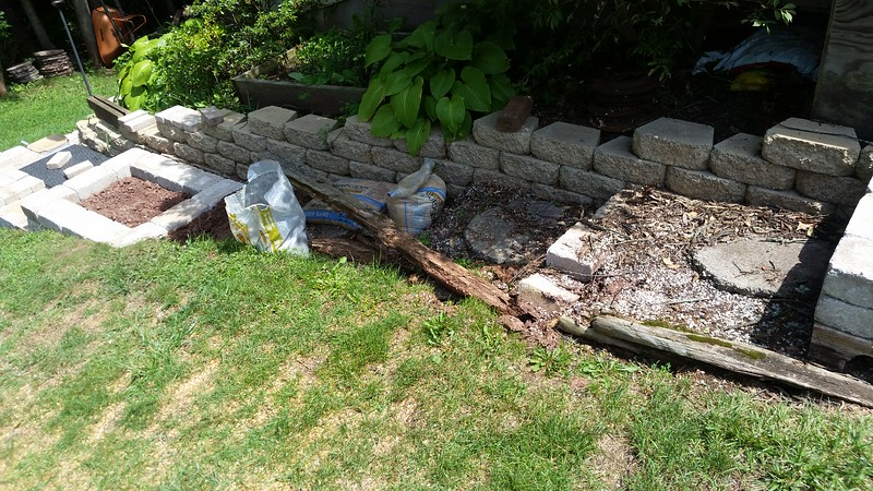 A before & after picture.  Before - rotting landscape timbers with white pebbles and large stepping stones.  After - block & brick.
