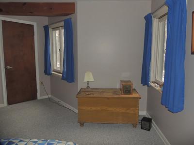 Lower level bedroom (#4) with closet door and  windows facing west.