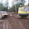 Trailer with blocks, excavator, and garage awaiting installation of the Stoneterra wall.