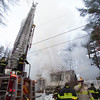 Firefighters use a hose attached to a ladder to suppress flames visible through the roof of 15 Georgiana Road in Billerica Thursday. Lowell Sun/Chris Lisinski