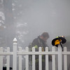 A firefighter adjusts his gear while working at the scene of a house fire on Georgiana Road in Billerica Thursday. Lowell Sun/Chris Lisinski