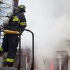 A firefighter surveys the smoke while battling a house fire at 15 Georgiana Road in Billerica Thursday. Lowell Sun/Chris Lisinski