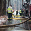 Firefighters stand in a large puddle on Georgiana Road after hoses were used to fight a house fire Thursday morning. Lowell Sun/Chris Lisinski