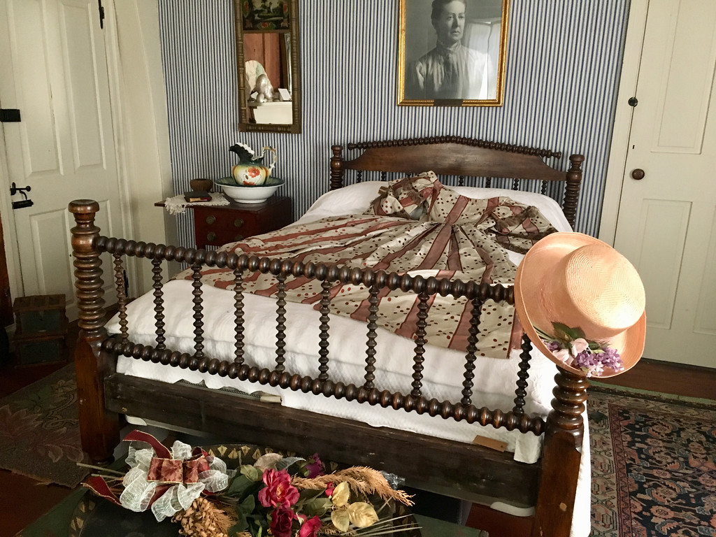 . A portrait of Clara Sexton, for whom the house is named, hangs over an spindle bed with a dress from the 1800s draped across it. Photo by Mary Leach