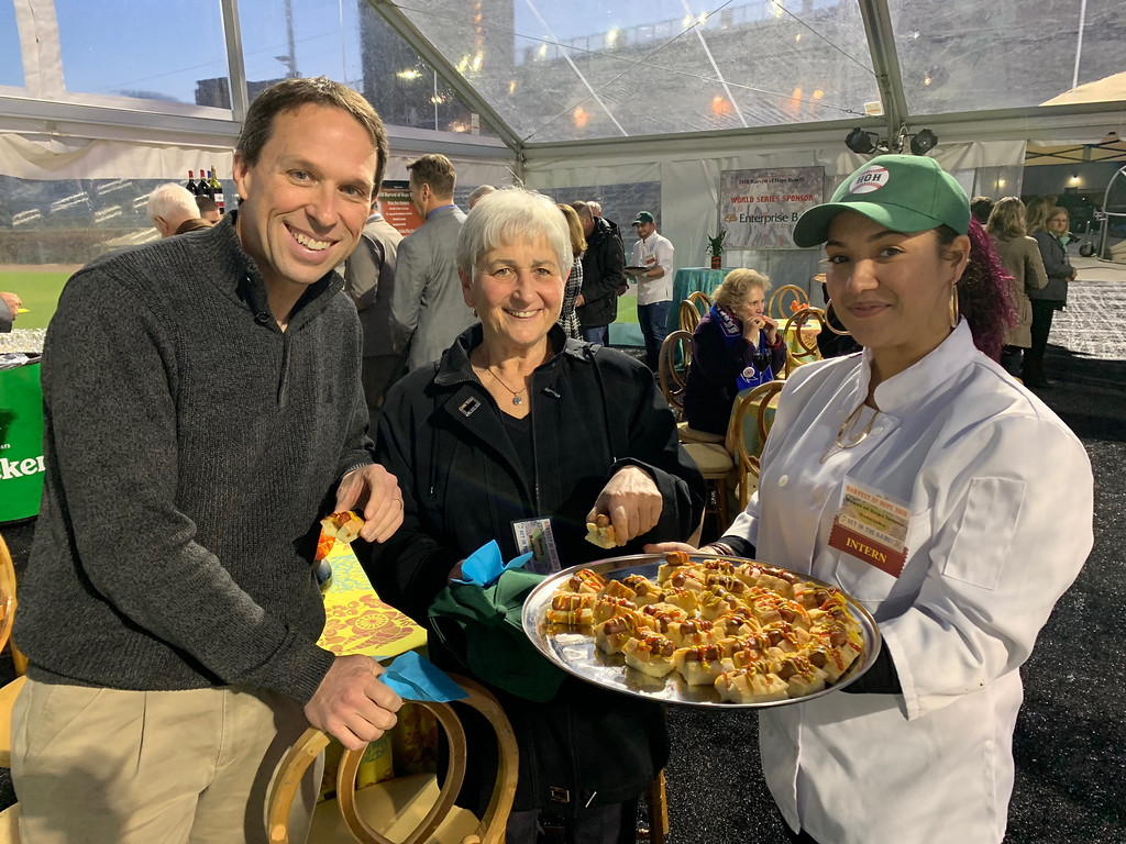 . Tod Smith of Chelmsford and Nancy Bartman of Burlington enjoy miniature hot dogs served by House of Hope intern Natascha Bracetty of Lowell.
