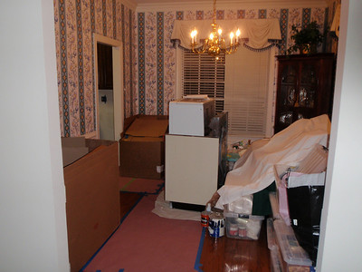 Dining Room filled with cabinet boxes and old appliances and contents of kitchen in tubs
