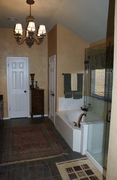 Master bath with frameless glass shower, tub, toilet to the right. One of the walk-in closets at end.  Sinks and cabinets are to the left.