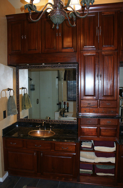 Left sink and center section of cabinets (mahogany with black granite counters and hammered copper sinks).