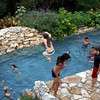 View of waterfall across pool with kids jumping off grotto roof.