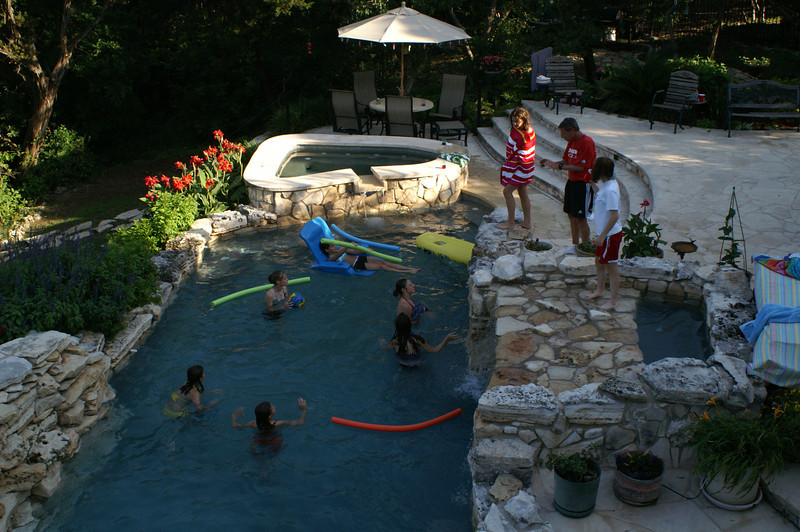 View of pool from main level deck waterfall on left, grotto/source pond on right and hot tub at upper middle.
