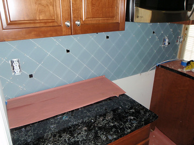 08/03 - Final tiles installed on stove wall.