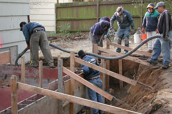 Pouring the foundation. They pumped the concrete up from truck parked on the street.